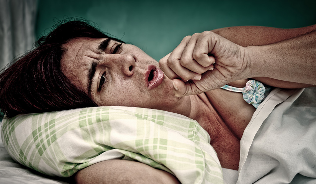 A woman sick with the flu in bed, coughing.