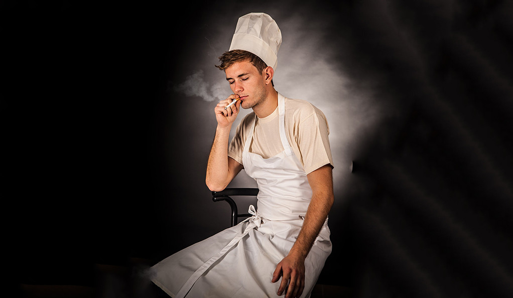 A man in a chef uniform smoking a cigarette