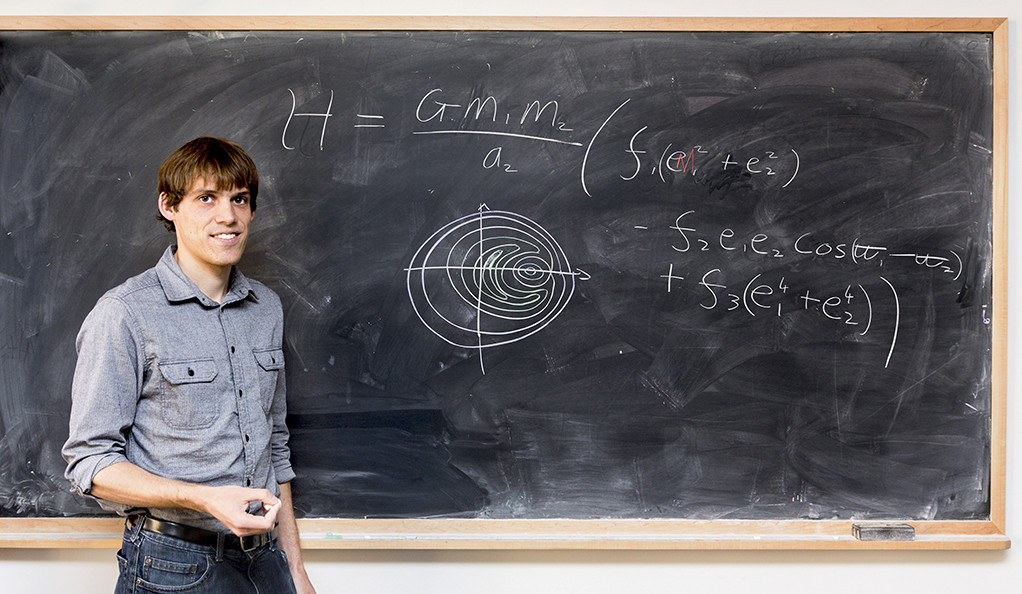 Photo of Christopher Spalding standing before a blackboard.