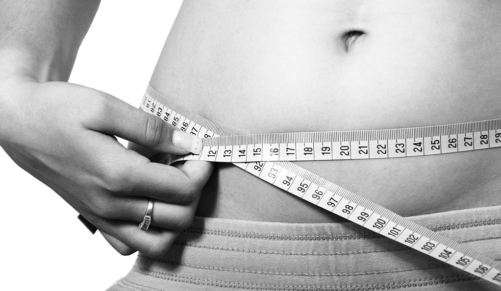 A black and white photo of a woman measuring her belly with tape.