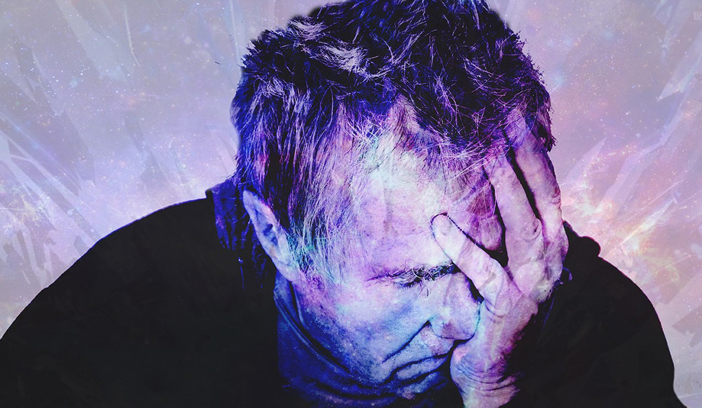 A stylized photo of a middle aged man exhibiting stress by clutching his head