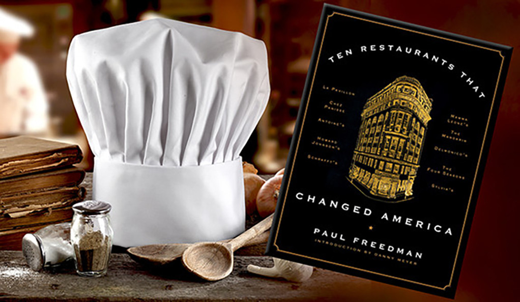 A chef hat and the book Ten Restaurants that Changed America by Paul Freedman
