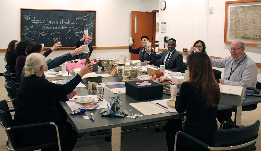 Beinecke staff toast the holiday seated at a table featuring culinary and other items from the library's collection.