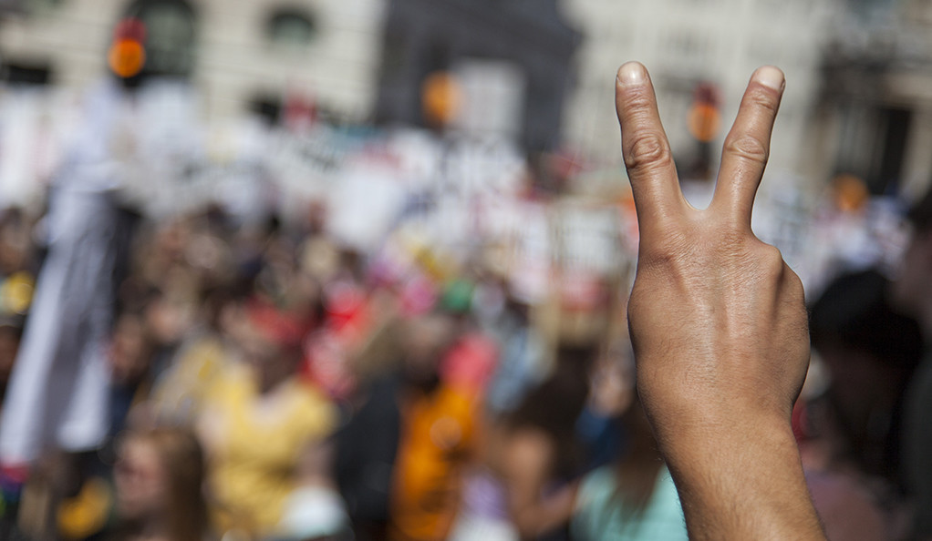 A peace sign held up at a political demonstration.