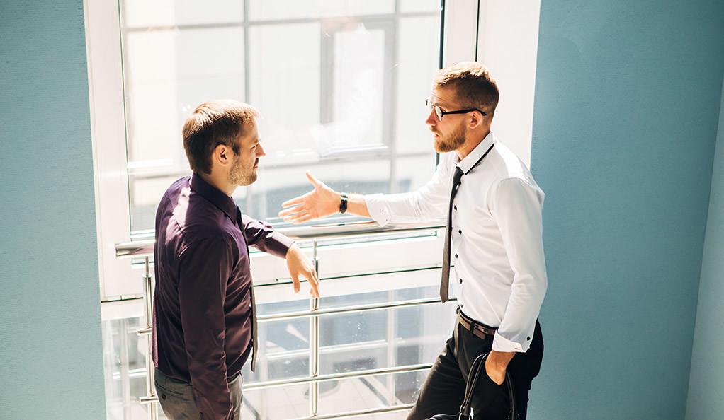Two men having a conversation in the lobby of an office.