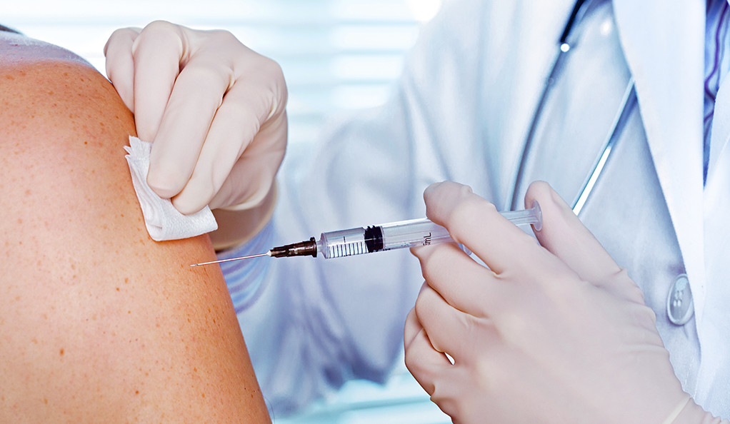 A photo of a doctor giving an injection into a patient's upper arm.