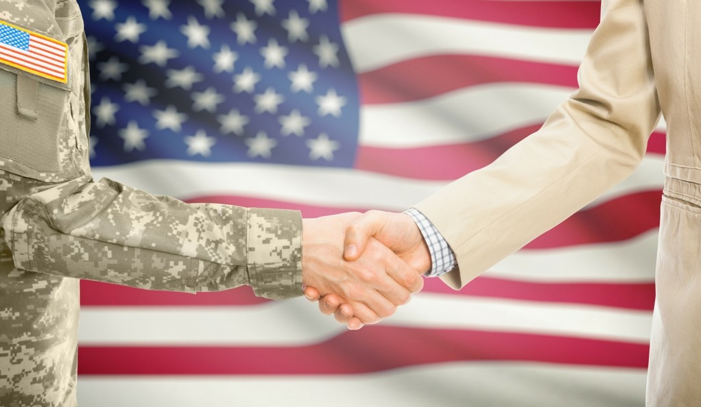 A man in a U.S. military uniform and a man in a civilian suit shake hands with the American flag in the background.