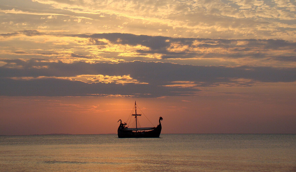 A viking longship on the open ocean at sunset.