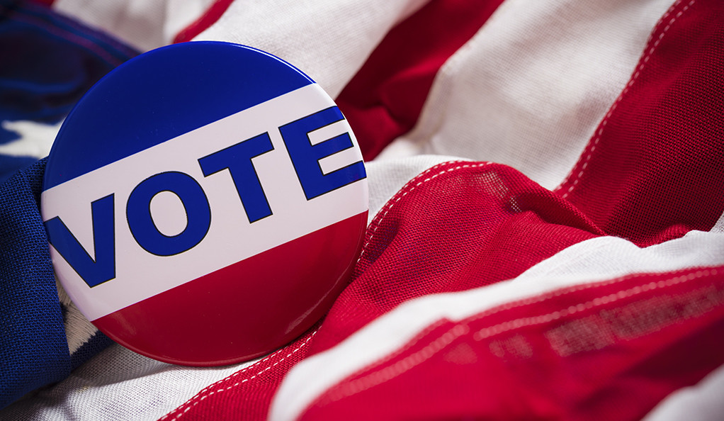 A VOTE button or pin resting on an American flag.