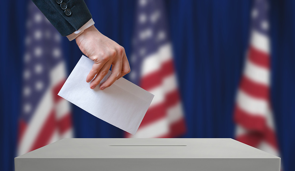 Election in United States of America. Voter holds envelope in hand above vote ballot. USA flags in background. Democracy concept