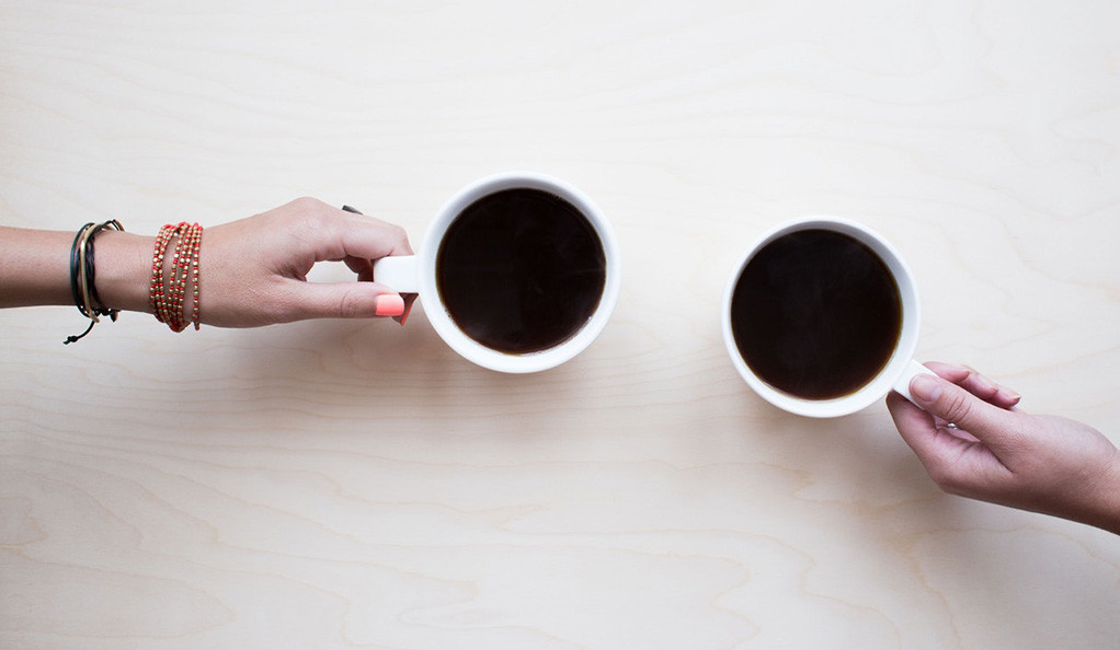 Two hands holding cups of coffee on a table, photographed from above.