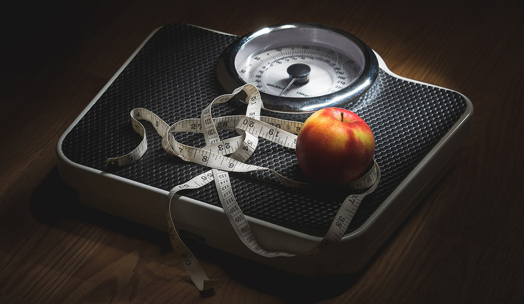 A bathroom scale with an apple and measuring tape on top.