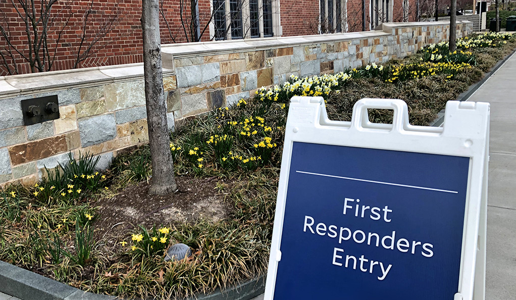 "A sign, ""First Responders Entry,"" next to a flower bed."