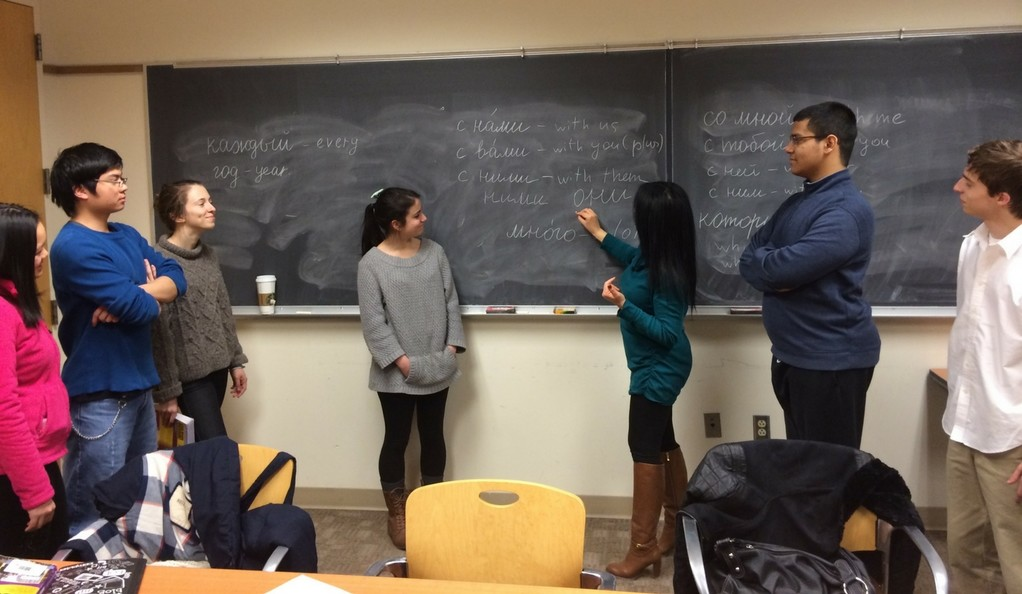 A group of high school students studying Russian text on a chalkboard.
