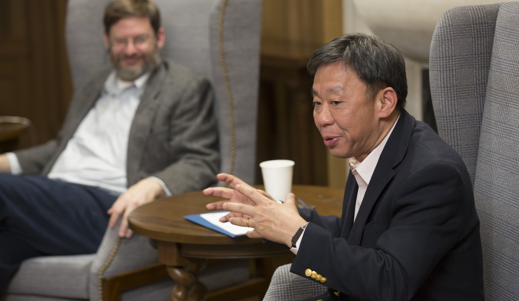 Two men sitting in arm chairs having a conversation