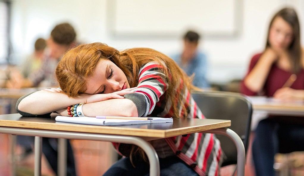 A teen girl sleeping in class