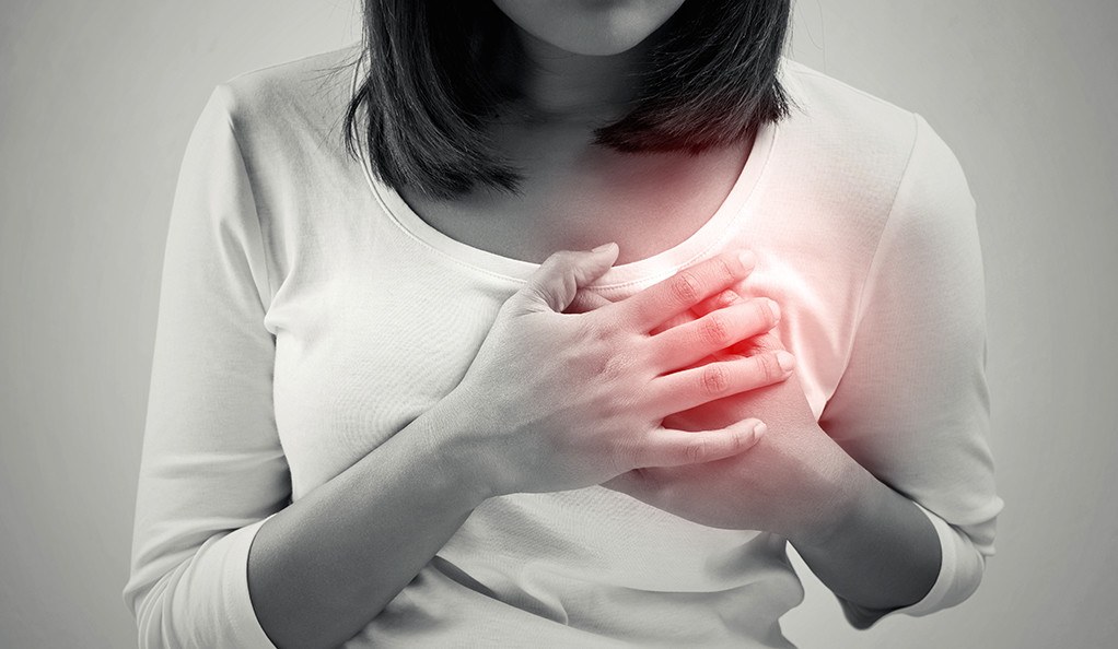 A black and white photo of a woman clutching her chest, with the area of the heart highlighted in red.