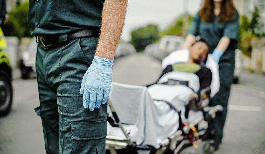 A woman on a ambulance gurney.