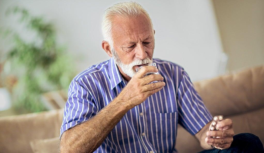 A senior man taking a pill