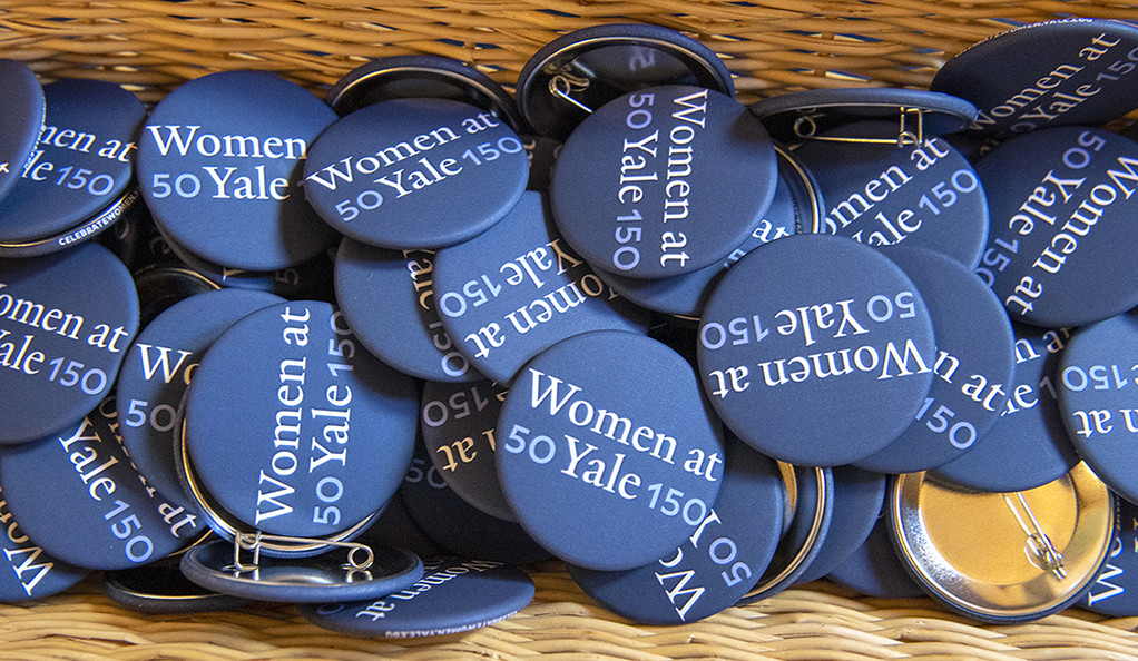 A basket full of buttons with the 50WomenAtYale150 logo on them