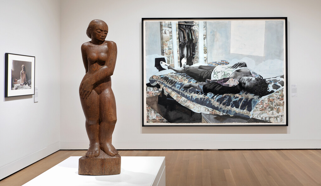 Wooden sculpture of female form with two paintings hanging on walls in the background.