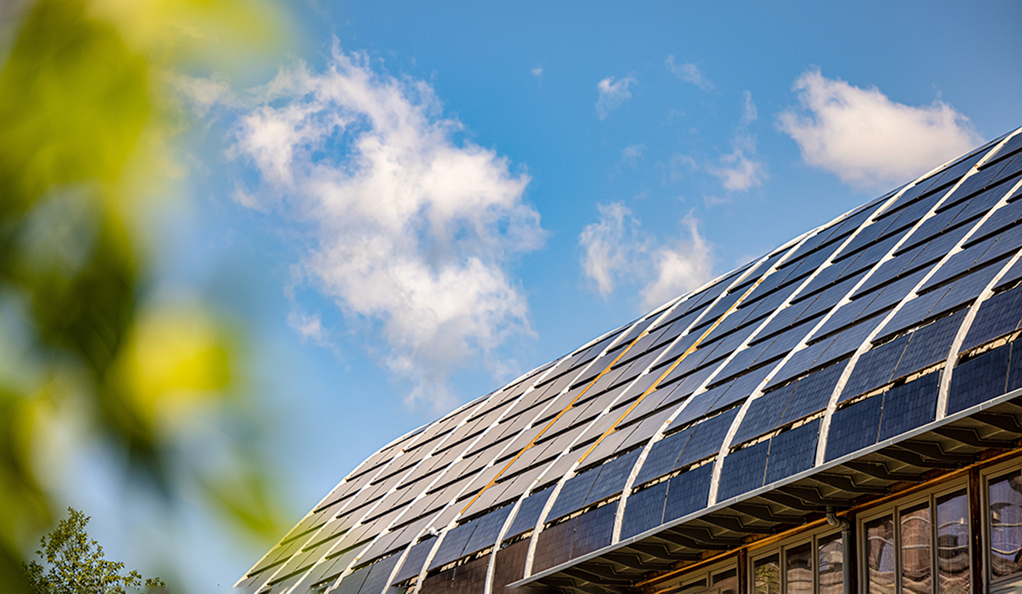 Solar panels atop Kroon Hall with blue sky in background