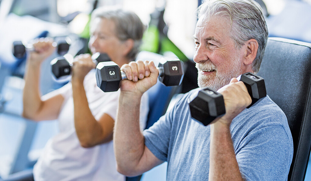 Two senior citizens lifting weights
