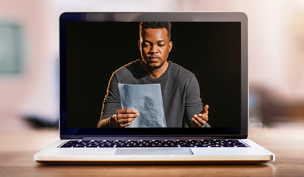 A young man reading a poem on a laptop screen