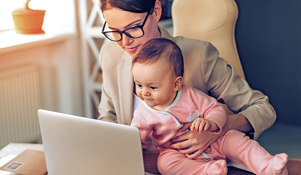 A stock image of a mother working on a laptop computer with a baby on her lap.