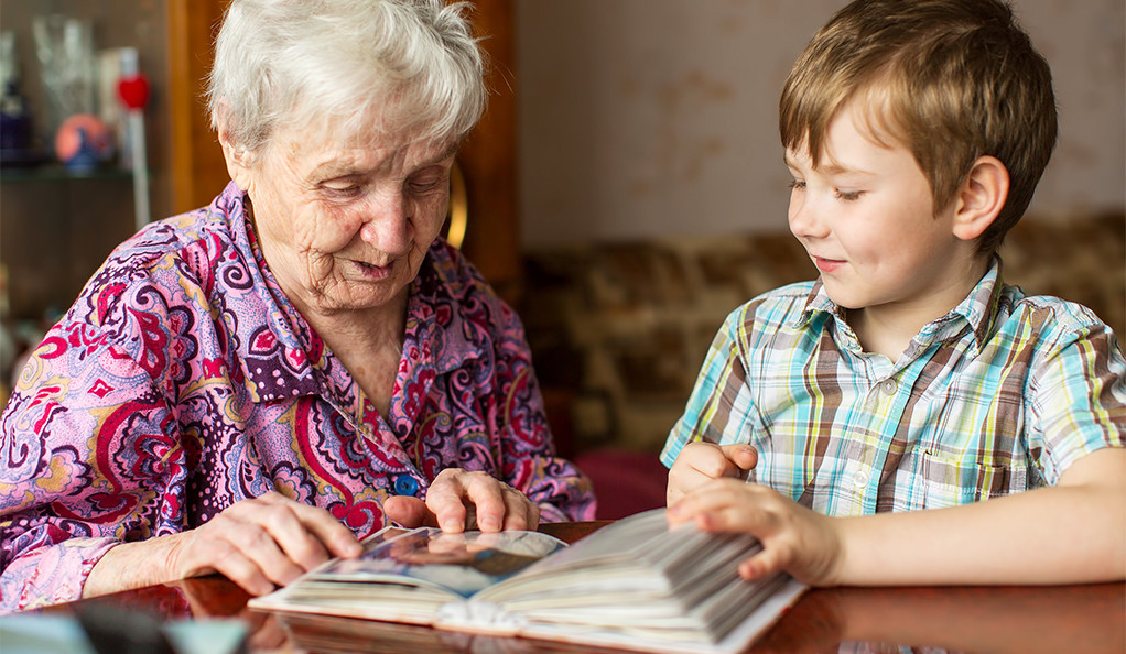An elderly woman looking at a photo album with a young boy.
