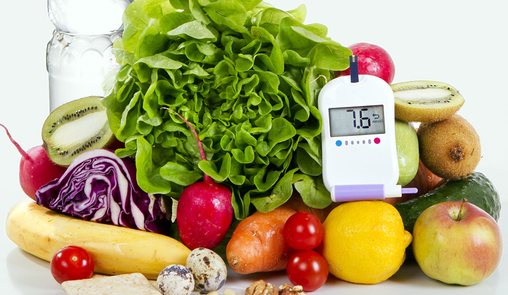 A stock photo of fruits and vegetables, with a diabetic blood sugar testing device.