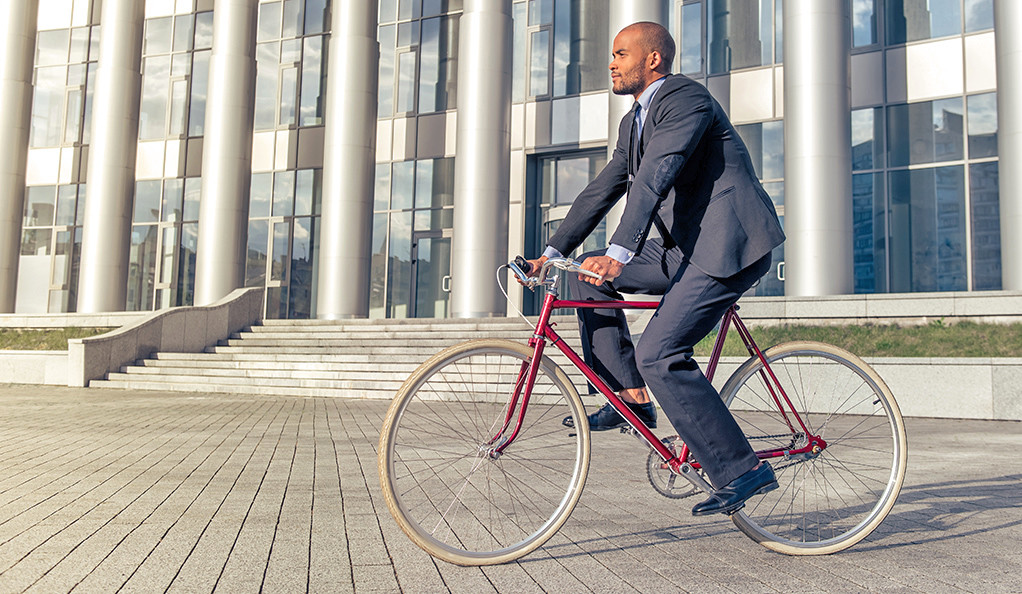 A stock photo of a black adult male riding a bicycle.