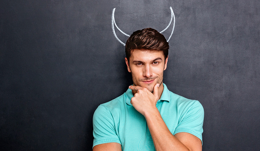 A man stroking his chin with devil horns drawn in chalk behind his head.