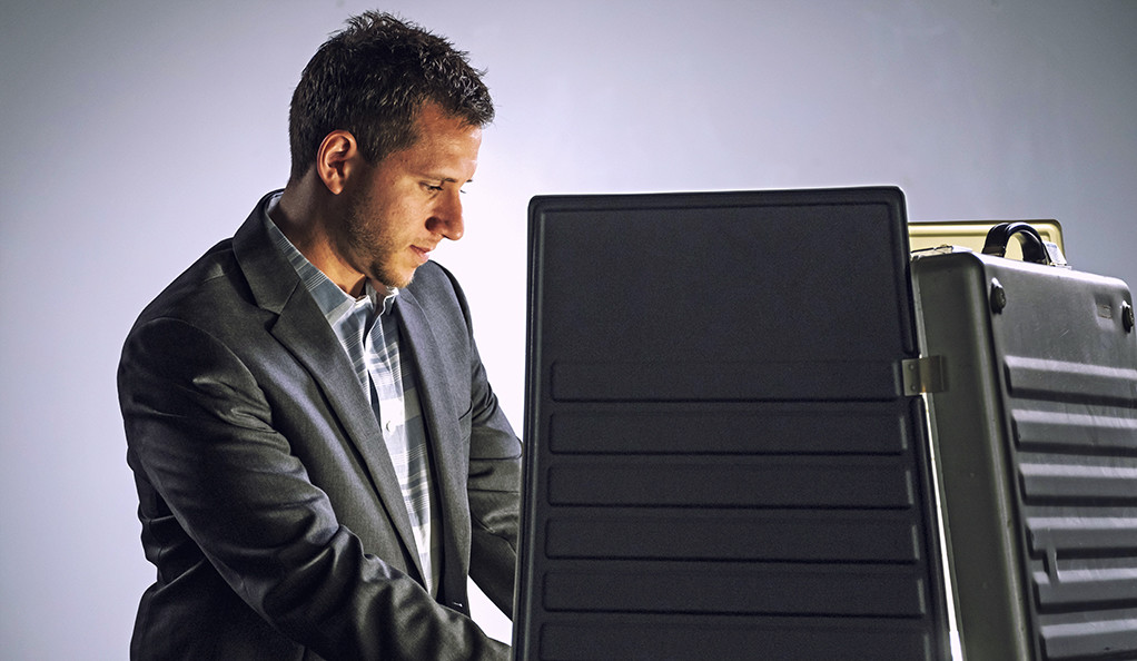 A stock photo of a white male at a voting machine.