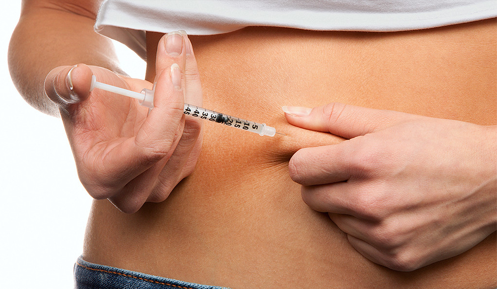 Stock photo of a syringe being inserted into a woman's stomach.