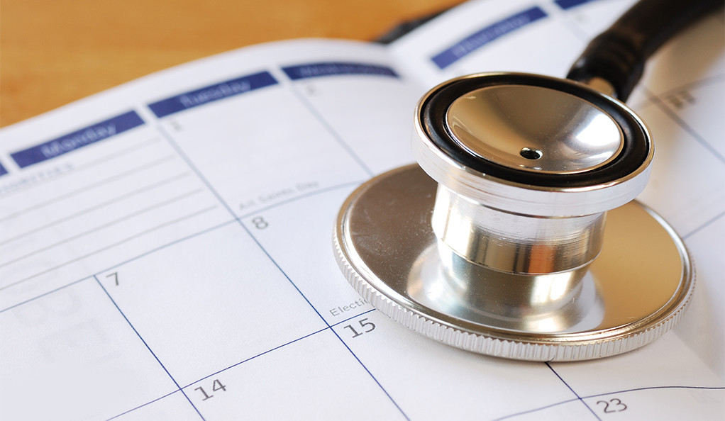 A stock image of a stethoscope and a calendar.