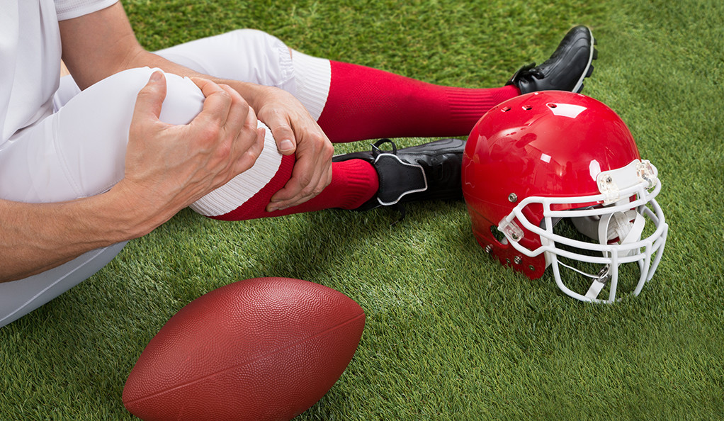 A photo of a football player sitting on a field and holding his right knee.