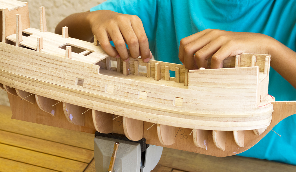 Child building small wooden boat