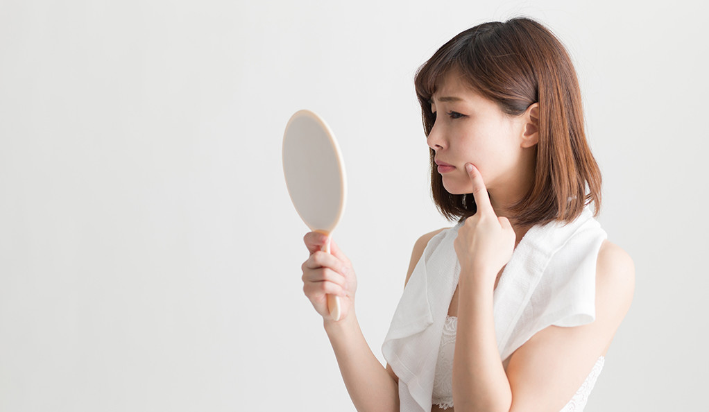 A young woman looking at herself in the mirror, pouting