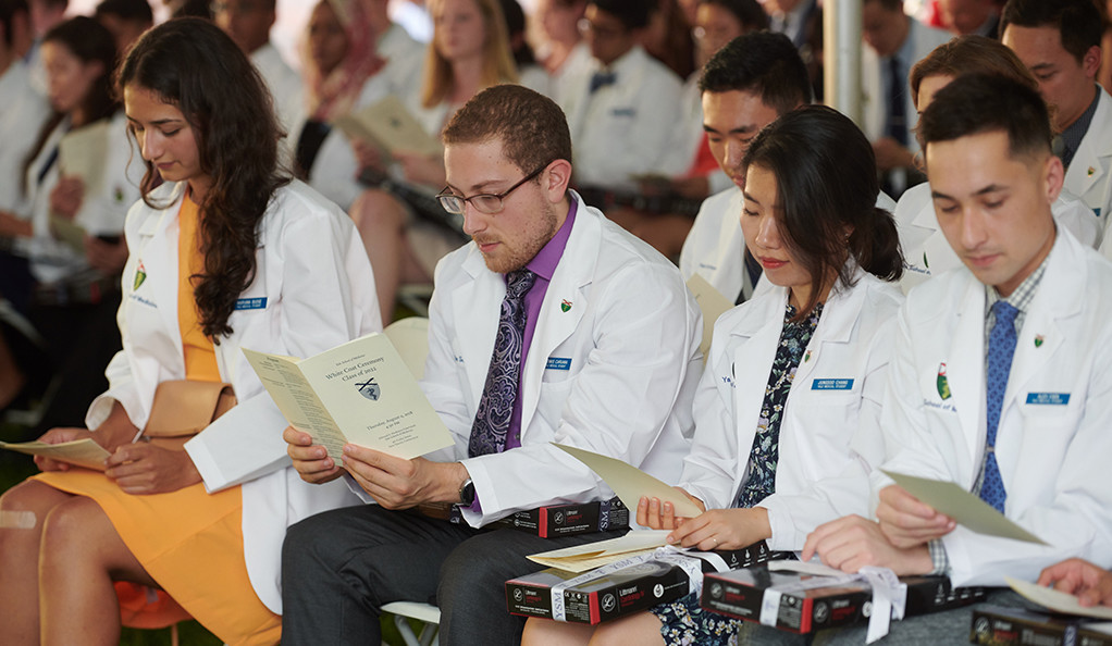 Students in their white coats at a Yale School of Medicine commencement ceremony.