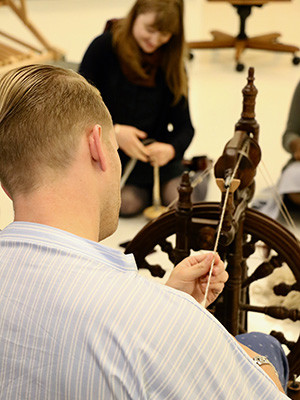 Workshop participants tried various methods of spinning wool, including with hand spindles and with a spinning wheel.