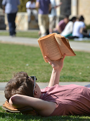 A Yale student laying in the grass on campus and reading an old paperback.