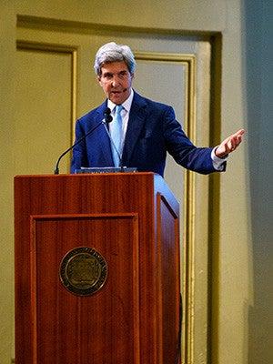 John Kerry speaking at a podium at Yale.