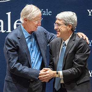 William Nordhaus and Yale President Peter Salovey shake hands at a press conference in honor of Nourdhaus' Nobel win.