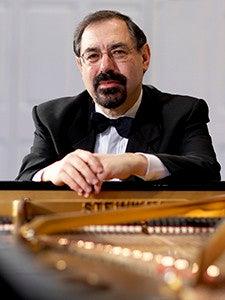 Pianist Boris Berman sitting at a piano.