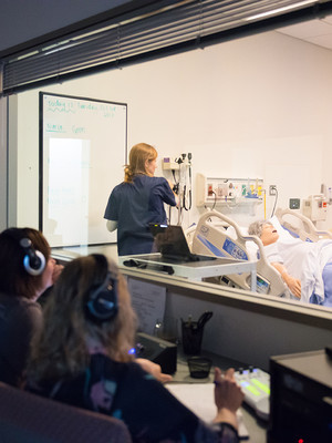 People sitting at computers, observing a clinical simulation through a large glass window.