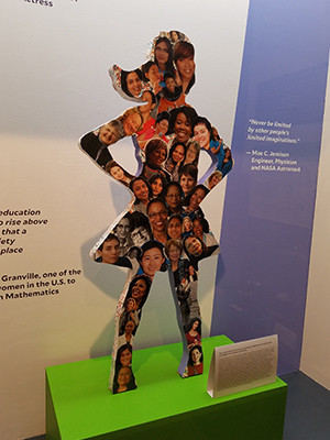 A display inspired by the Fearless Girl statue, with a collage of women's faces and inspirational quotes.