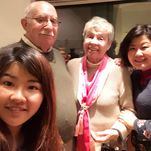Ron Heiferman and his wife (center) pose with two international students they hosted.