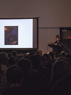 Hito Steyerl delivering a lecture with a slide of Leonardo's painting 'Salvator Mundi'