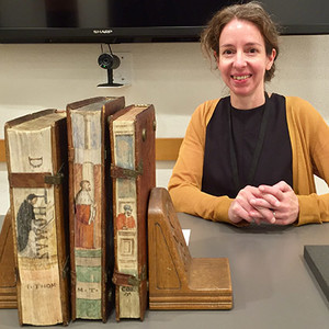 Three ancient books stand upright in the foreground, with Beinecke curator Kathryn James in the background.